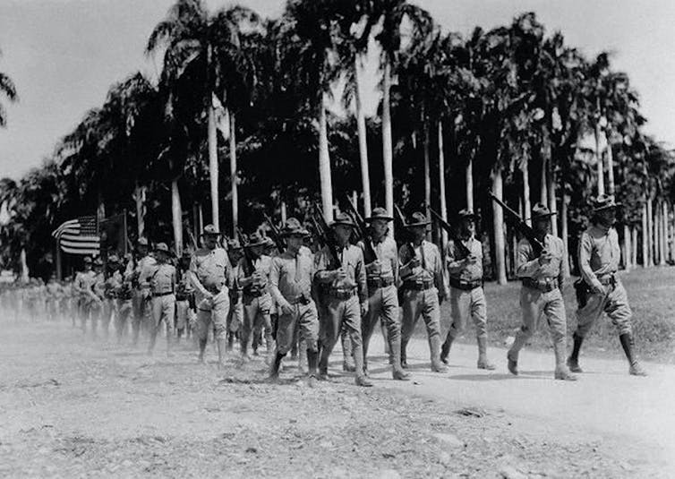 Marines march with palm trees in the background.