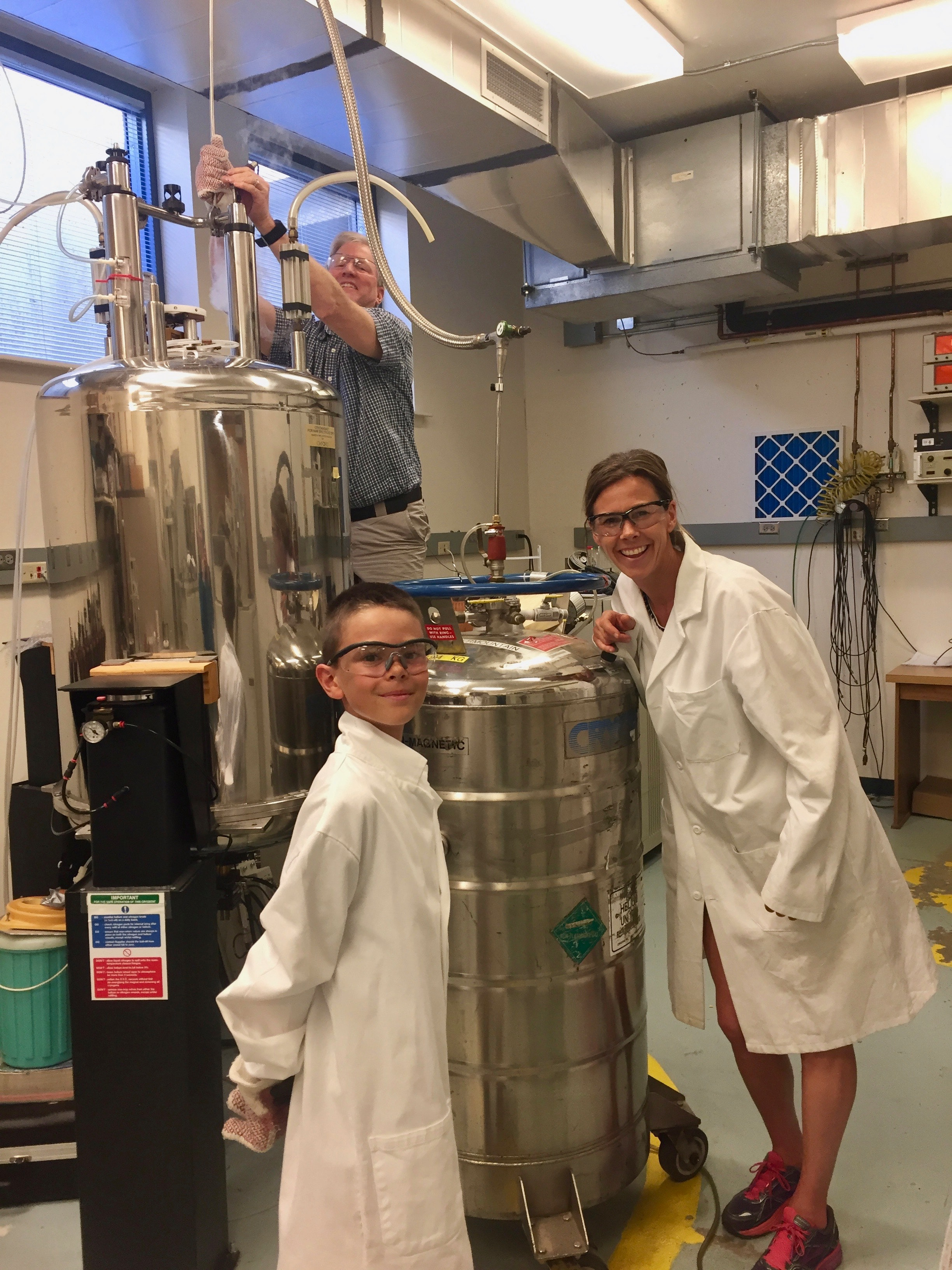 Woman and boy in lab coats next to helium tanks.