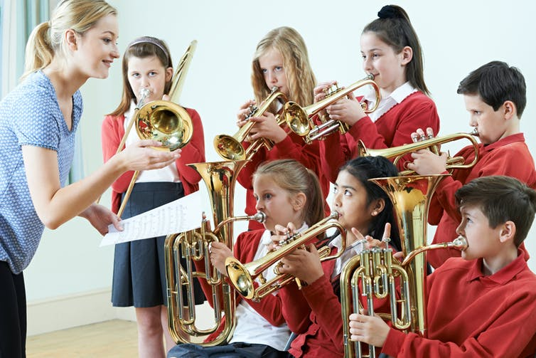 Pupils in uniform playing brass instruments with their teacher