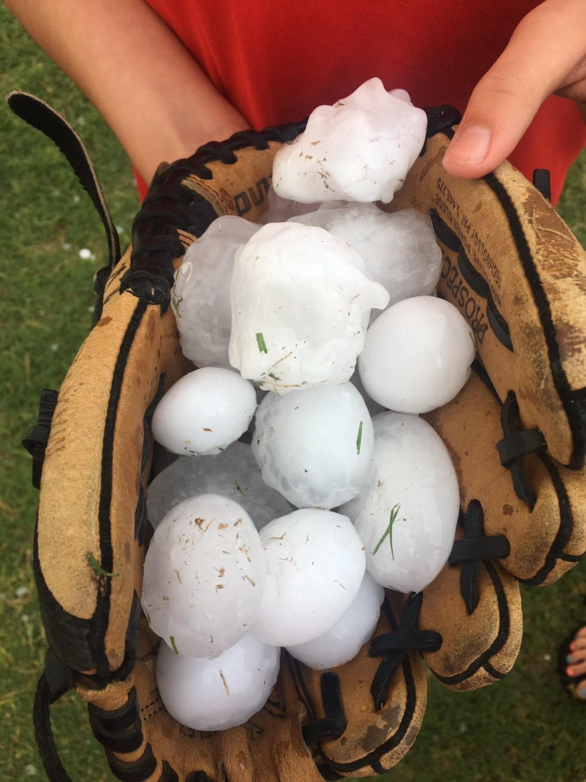 Large hailstones fill a baseball mitt