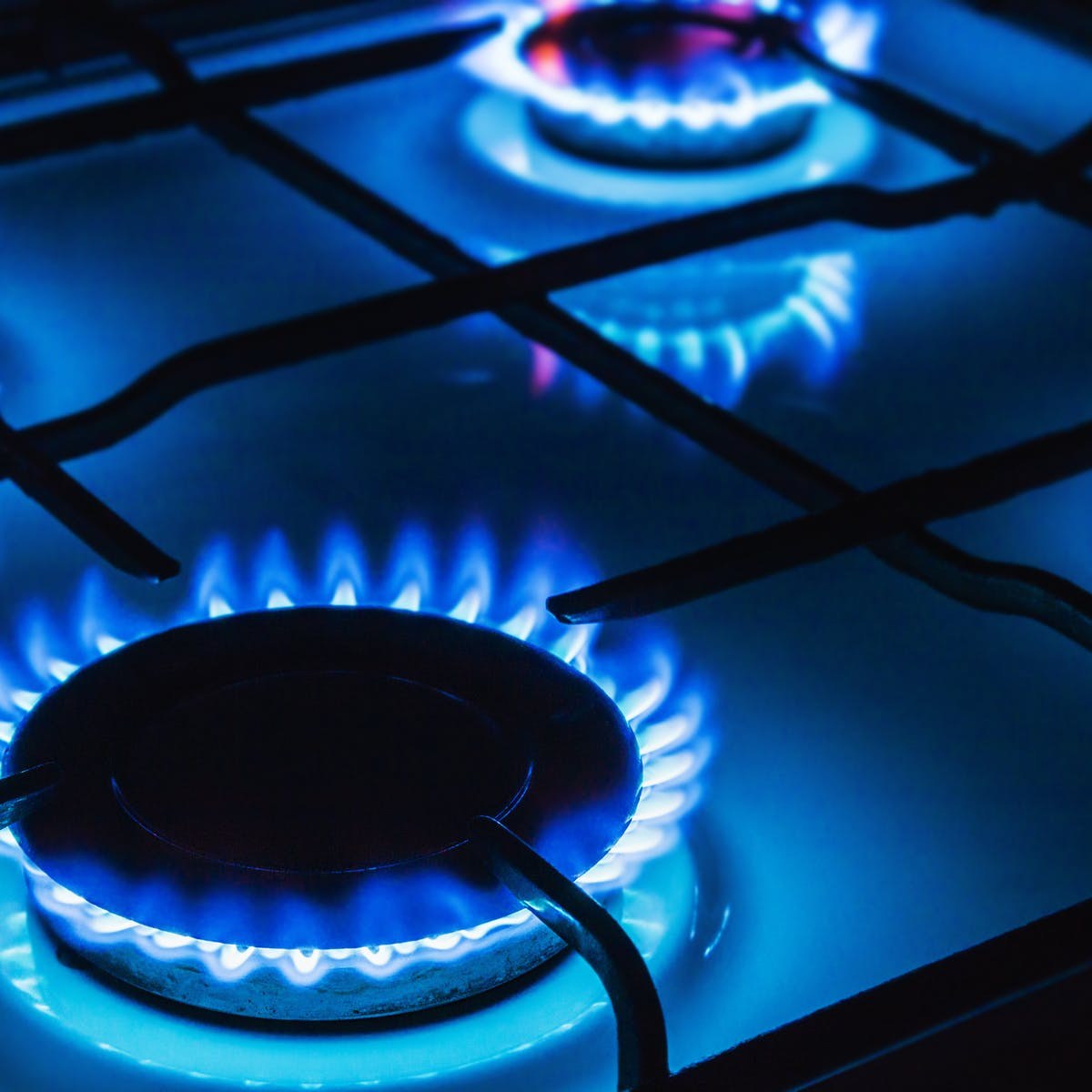 A gas stove with blue flames.