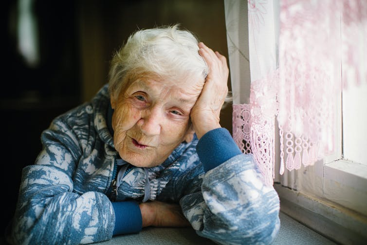 old woman sitting by a window