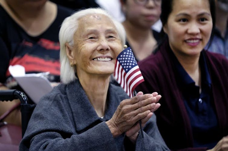 older Asian woman holding an American flag