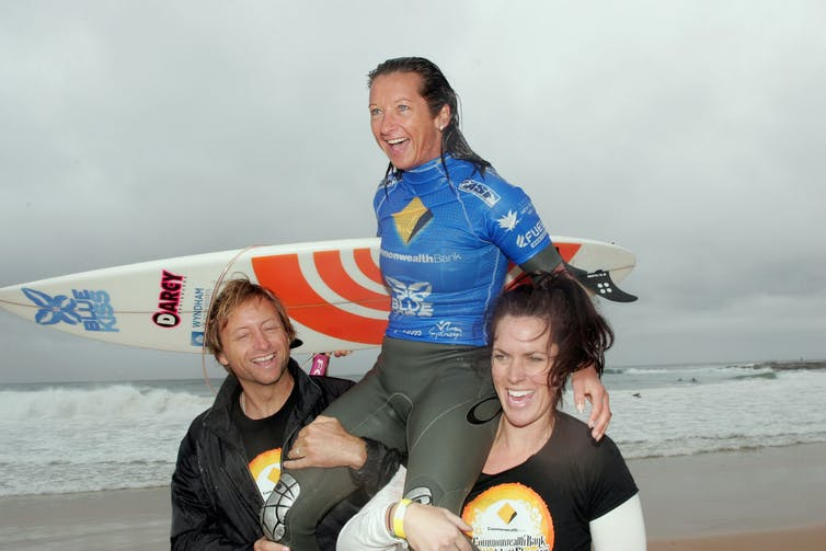 Women's surfing riding wave towards gender equity