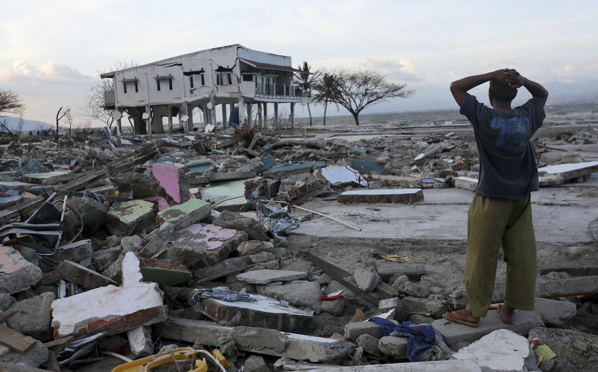 A man surveys the damage after the earthquake and tsunami.AP Photo/Tatan Syuflana