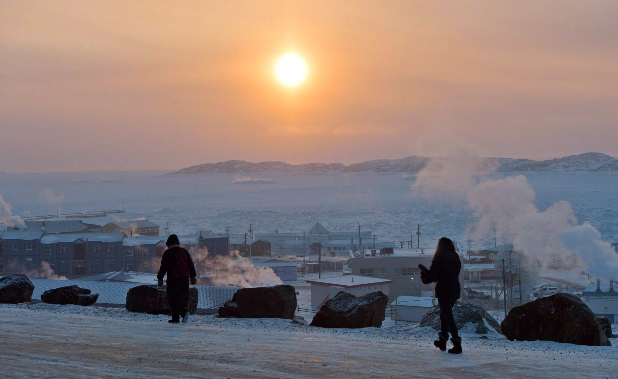 People walk along a path in Iqaluit, Nunavut in December 2014. - The Canadian Press