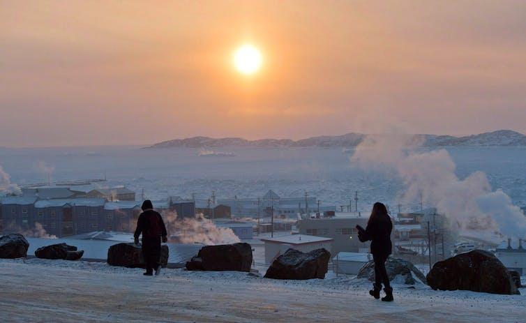 People walk along a path in Iqaluit, Nunavut in December 2014. - The Canadian Press