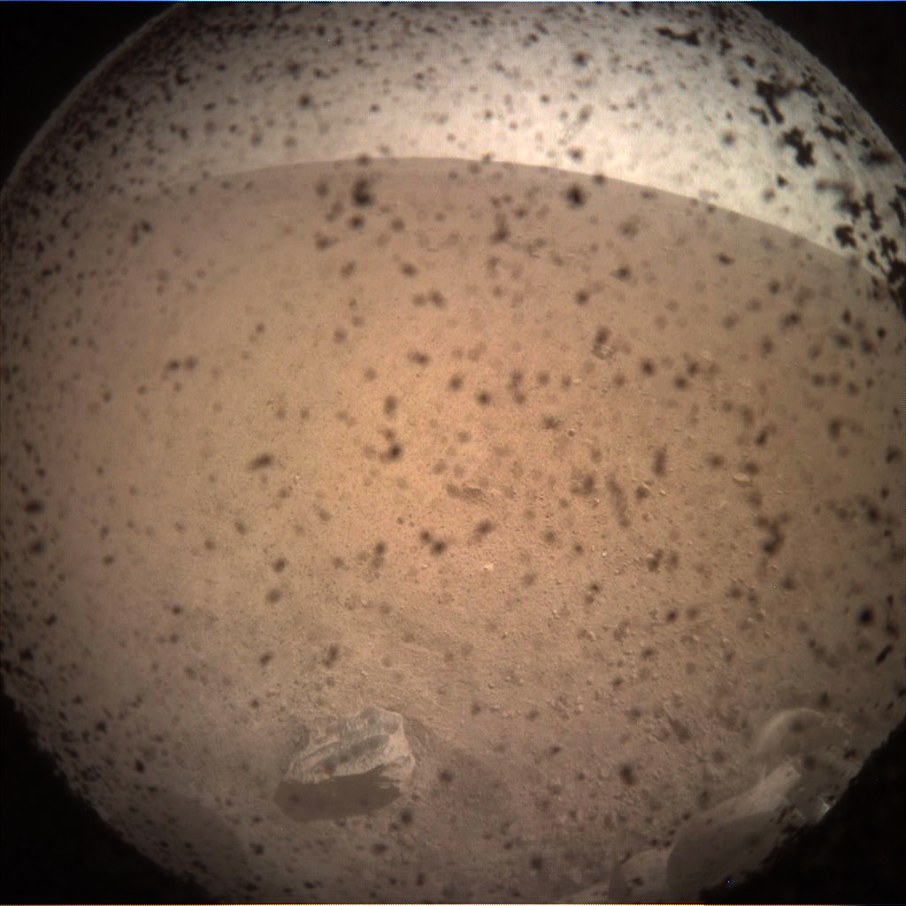 The first image returned from InSight. The black specks are on the protective transparent lens cover, which had not yet been removed. Credit: NASA/JPL-Caltech.