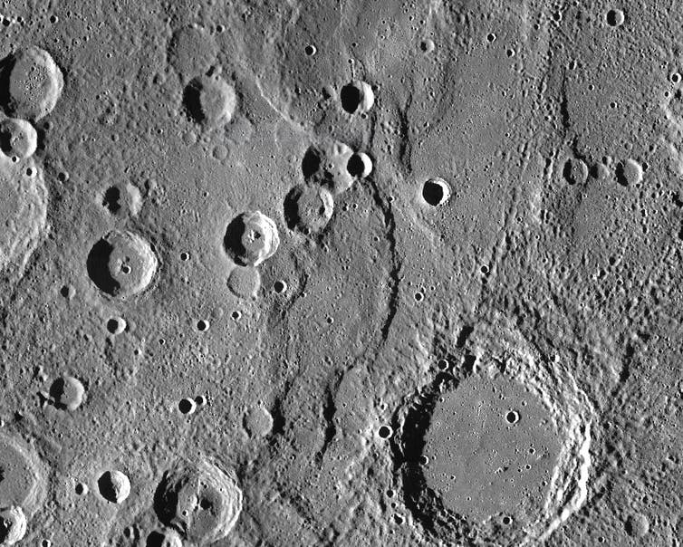 Close-up view of the terrain of Mercury. The image is dark grey and shows some raised mounds on the ground.