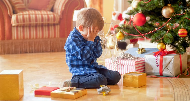 Child covering face by two hands in front of Christmas Tree