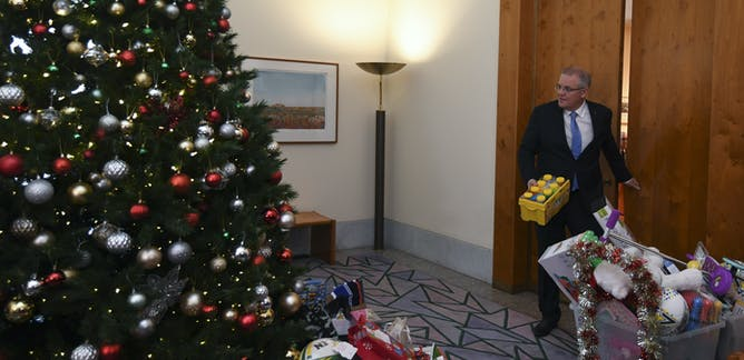 Prime Minister Scott Morrison puts a gift under the Salvation Army giving tree at his office in parliament house. Lukas Coch/AAP December 16, 2018