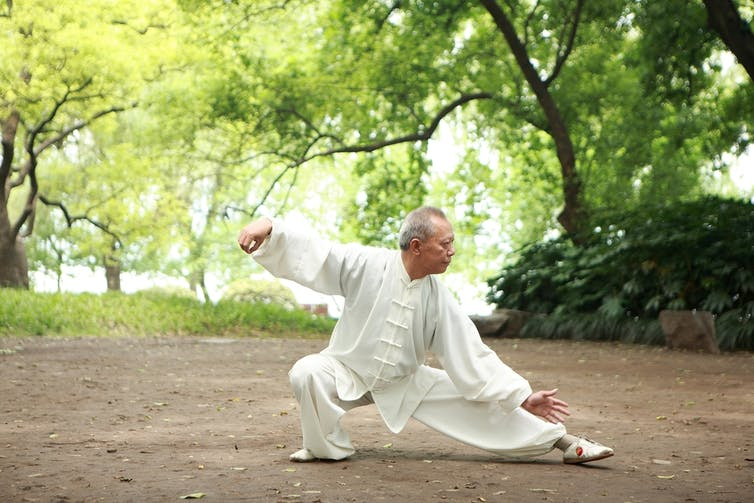 older-man-doing-tai-chi-in-garden-exercising-for-his-age