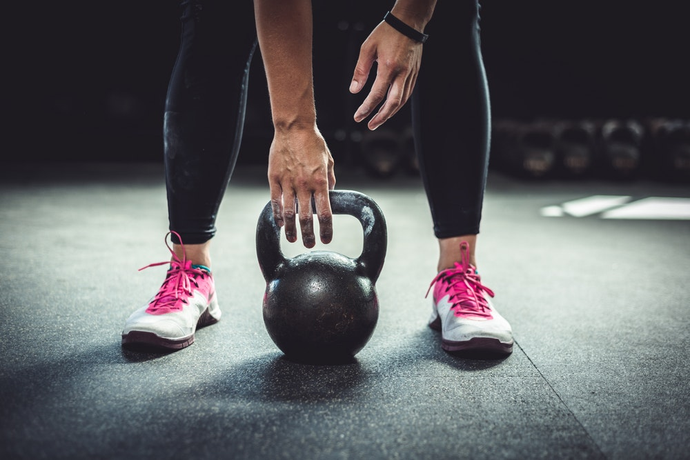 Take up kettlebells in your 40s to burn calories. Goolia Photography/Shutterstock