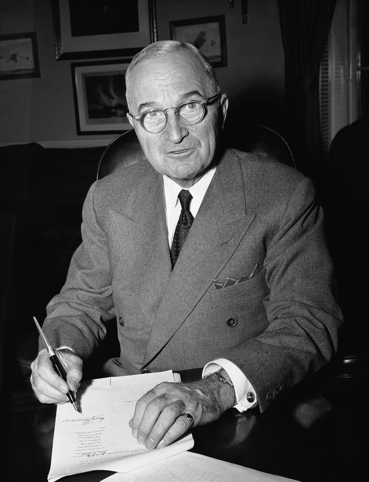 President Harry Truman in his White House office in Washington on Dec. 16, 1950 signs a proclamation of a state of national emergency, summoning the nation to marshal its strength against the threat of 'Communist world conquest.'  AP Photo/William J. Smith