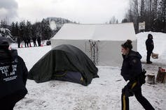 RCMP members gather at a Wet'suwet'en checkpoint to remove barriers on a bridge over the Morice River, southwest of Houston, B.C., on Jan. 11, 2019. Photo by Chad Hipolito, The Canadian Press