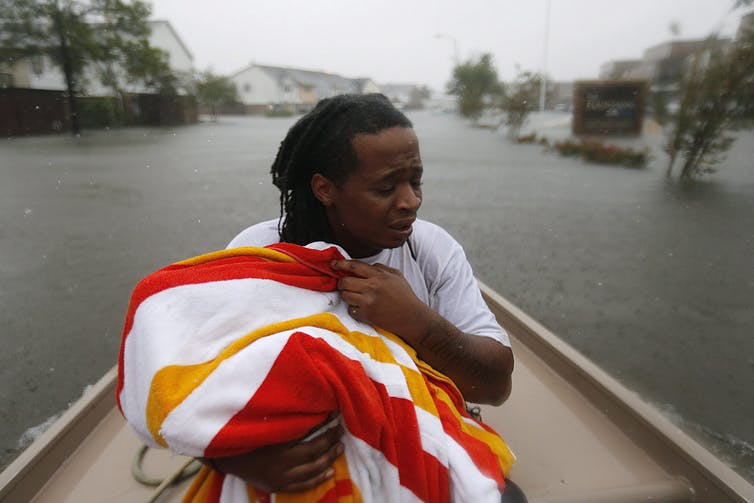 Demetres Fair holds a towel over his daughter, Damouri Fair, as they are rescued following Hurricane Harvey