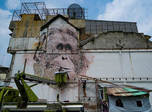 'Vhils', a Portuguese street artist, chisels an endangered orangutan onto a wall in the city of Medan, Indonesia.