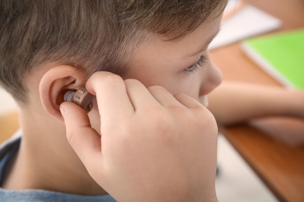 boy inserting a hearing aid