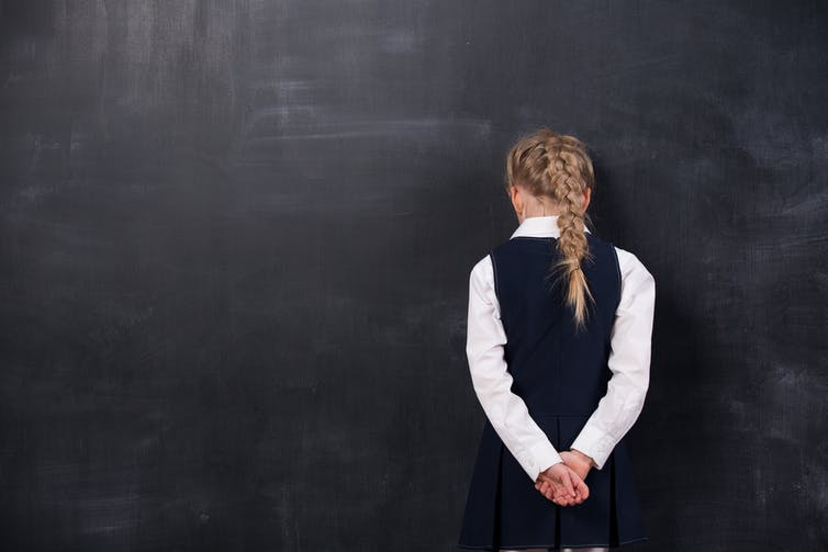 girl standing in front of a blank chalkboard