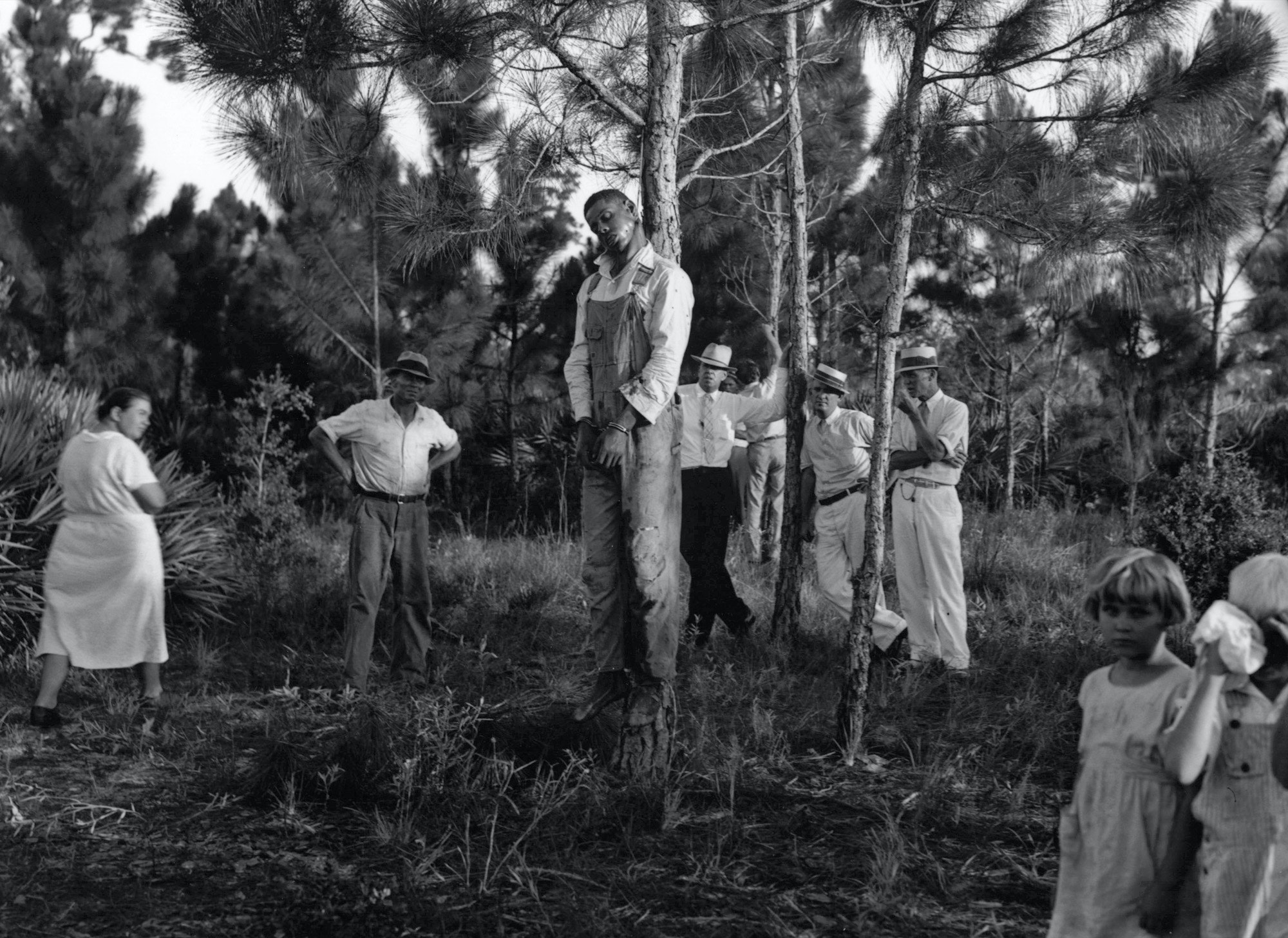 The body of Rubin Stacy, 32, hangs from a tree in Fort Lauderdale, Florida, as neighbors visit the site July 19, 1935. White lynchings of blacks were common during the era.