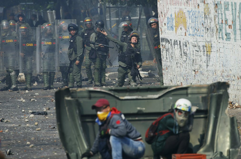 An officer from Venezuela s National Guard lobs tear gas toward  demonstrators during a standoff over humanitarian aid at the Colombian  border on Feb. 4ba8d9ea75046