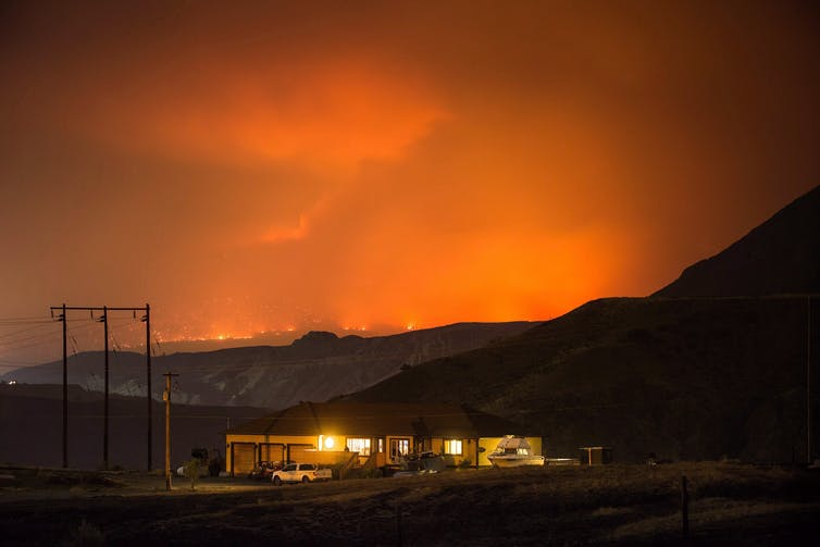 A home with lights on at dusk with the mountains in the background and the sky full of clouds of smoke glowing orange.