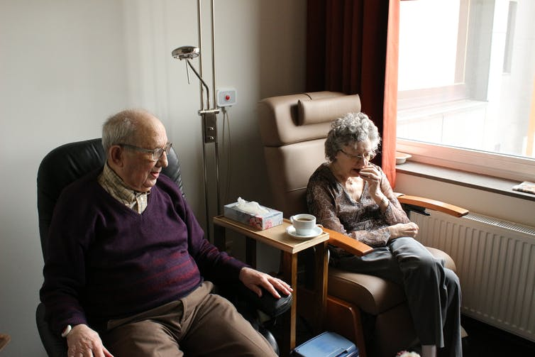 Image of elderly couple sitting in an aged care facility