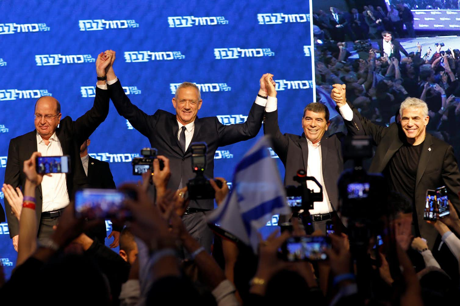Benny Gantz, head of Blue and White party, holds hands with his party candidates Yair Lapid, Moshe Ya'alon and Gabi Ashkenazi, as they react to exit polls in Tel Aviv, Israel on election day. Photo credit: Corinna Kern/Reuters