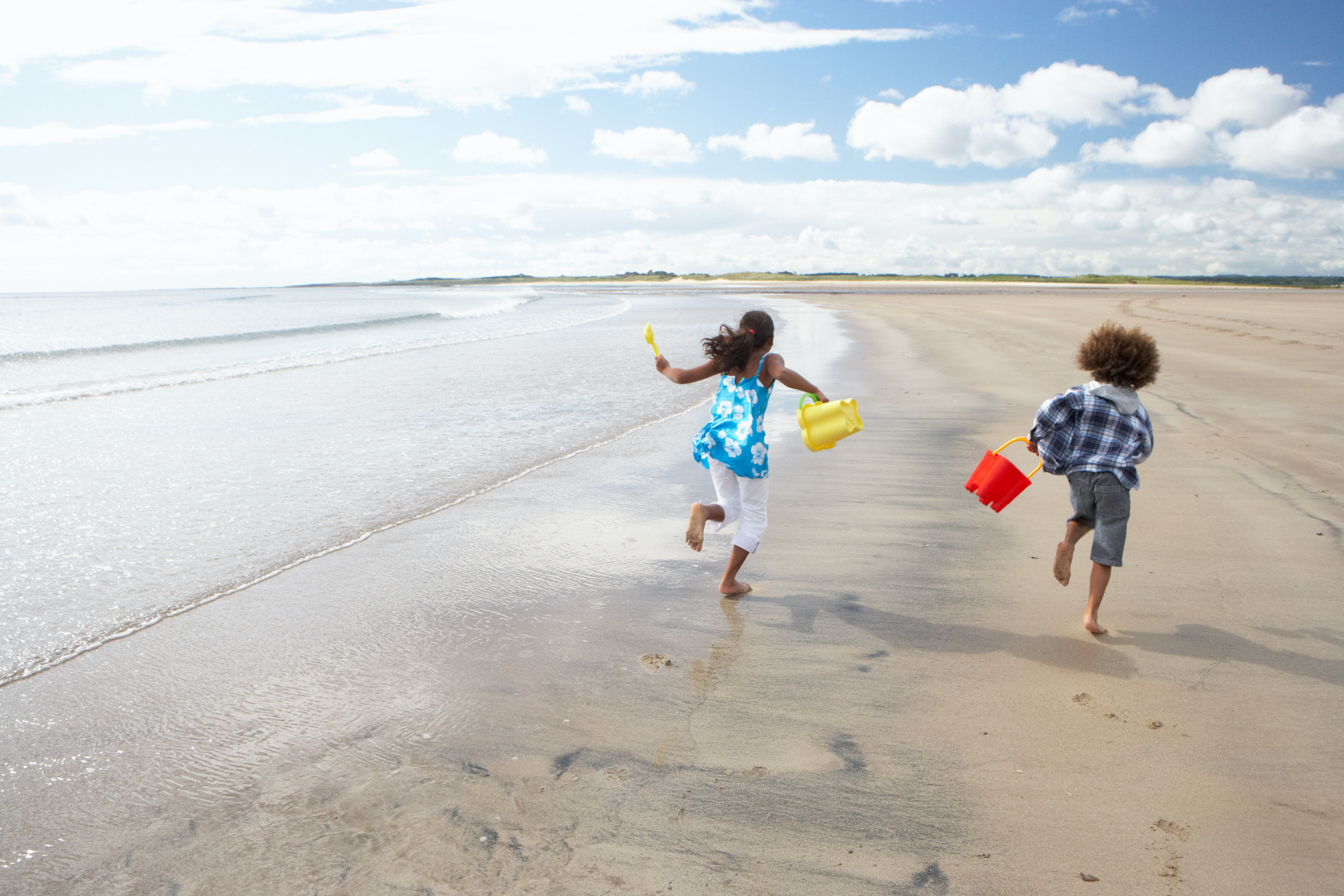 photo of two children running on a beach