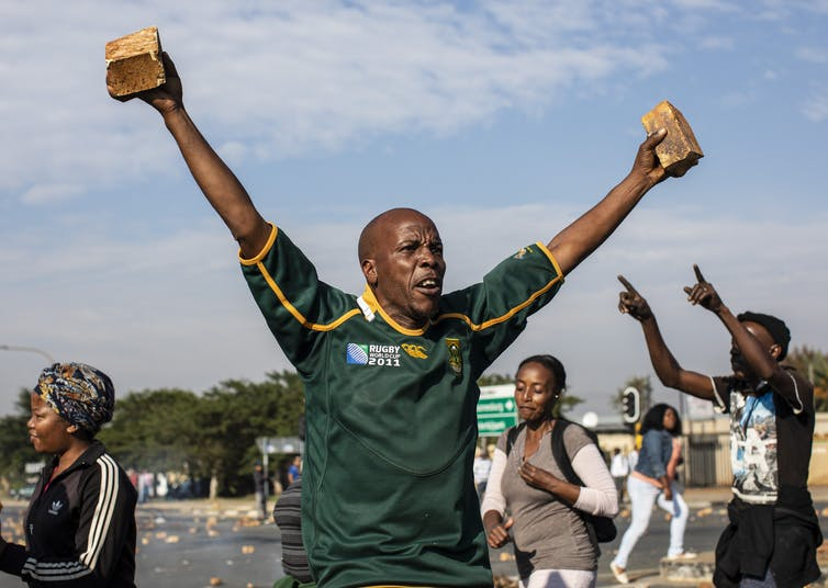 A man challenges police during a protest in Eldorado Park, Johannesburg.EPA-EFE/Kim Ludbrook