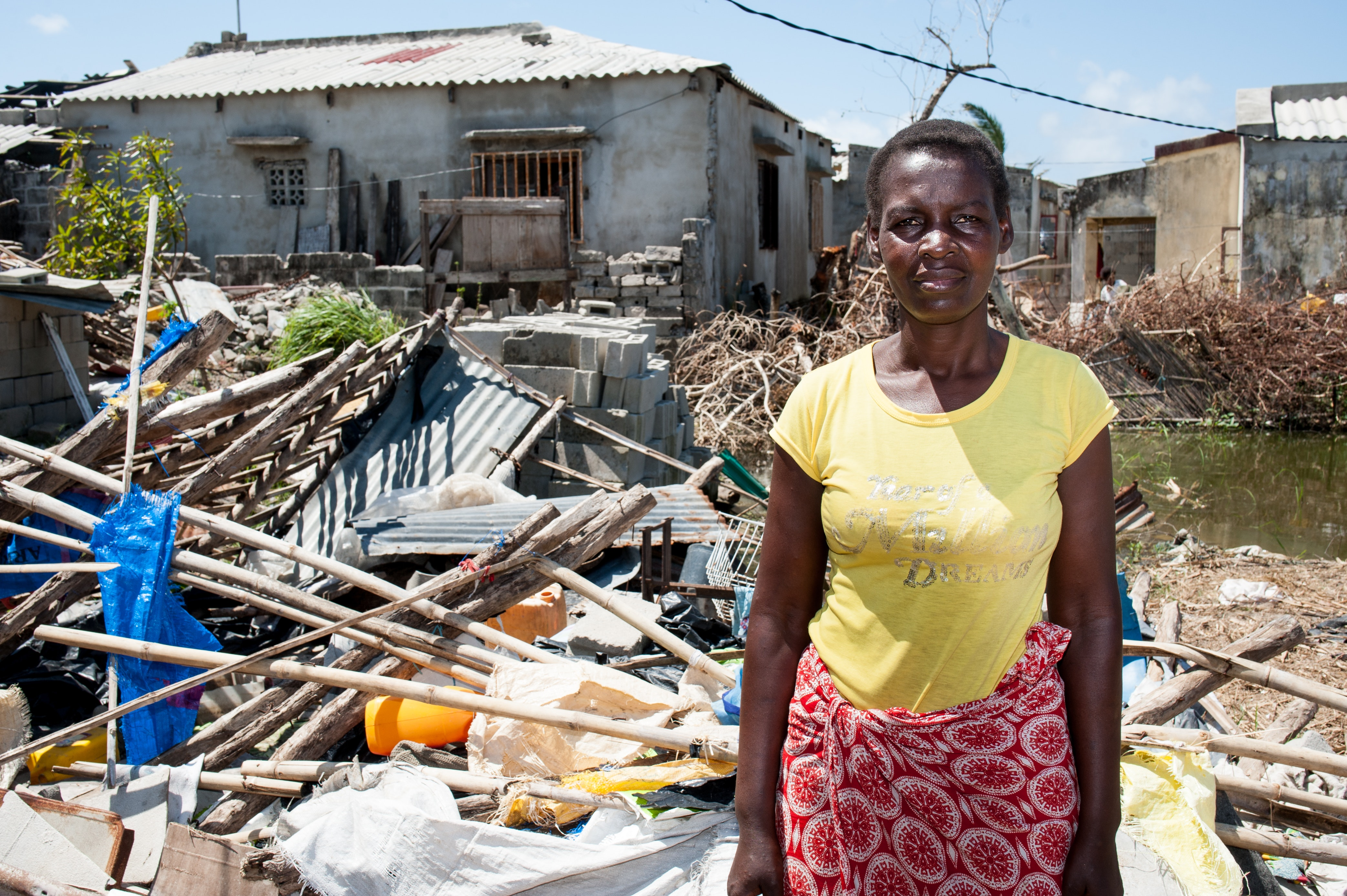 A Mozambican standing in front of her home, destroyed by Cyclone Idai. More than 1,000 people died in the storm. Photo credit: Christian Jepsen/flickr, CC BY-NC-ND