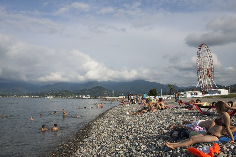 Tourists swim and sunbathe in the Black Sea resort town of Batumi
