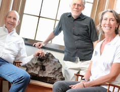 Drew Barringer (left), owner of Arizona meteor crater, his wife, Clare Schneider, and author William Herbst in the Van Vleck Observatory Library of Wesleyan University, where an iron meteorite from the crater is on display. W. Herbst