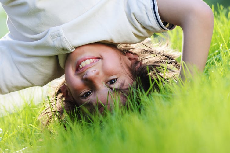 happy-child-playing-outside-in-the-grass-doing-a-headstand-smiling