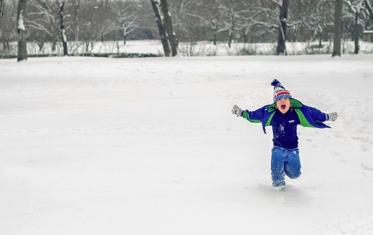 happy-toddler-playing-outside-in-the-snow-laughing-and-running