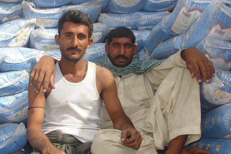 Deux ouvriers pakistanais, sur les docks de Deira, Dubai, 2010. Les expatriés d'origine sud-asiatique doivent montrer leur 'différence', leur 'occidentalité' pour dissiper le doute possible. Charles Roffey/Flickr, CC BY