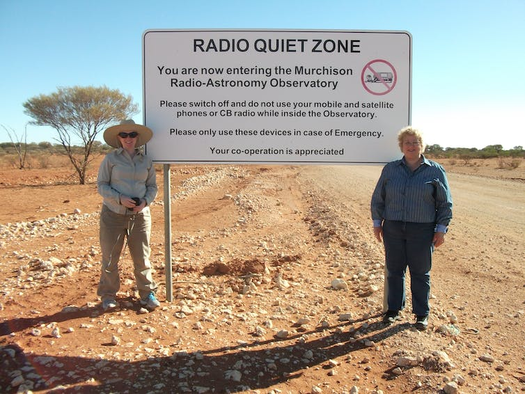 Two people standing by a sign saying Radio Quiet Zone.