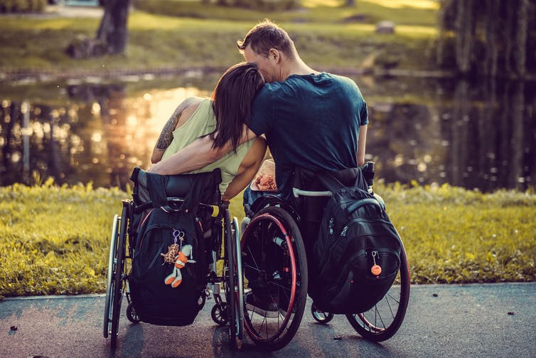 A couple, both in wheelchairs, embrace in a park.