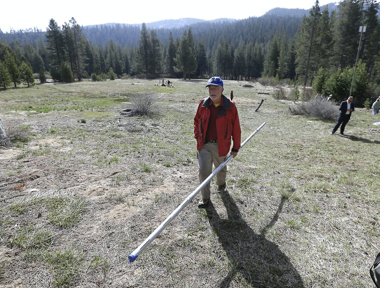 Frank Gehrke, chief of the California Cooperative Snow Surveys Program, carries a snow pack measuring tube near Echo Summit, Calif., on April 1, 2015 – the first time Gehrke found no snow at this location on this date. Source: AP Photo/Rich Pedroncelli