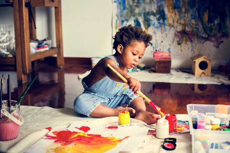 African American toddler painting on a wide sheet of paper in a nice flat