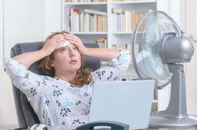 A woman sat at a desk with a large fan mops sweat from her brow.