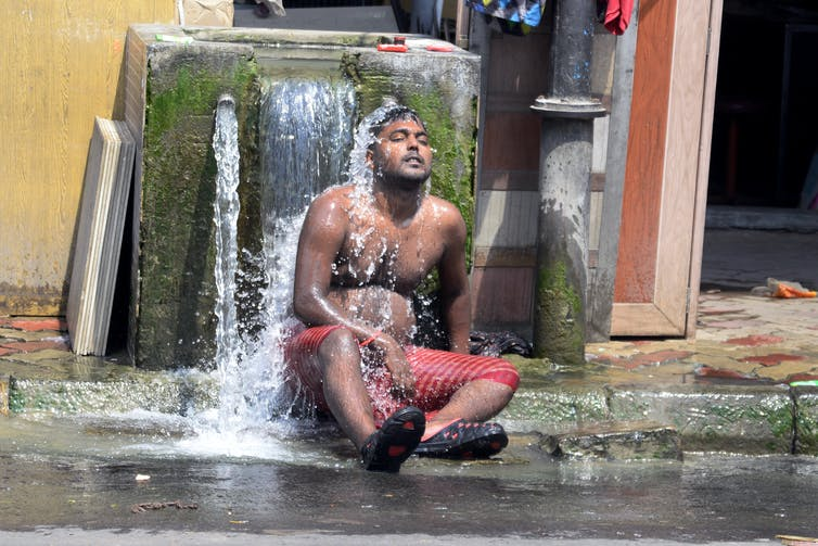 A shirtless man sits under a fountain to cool off.