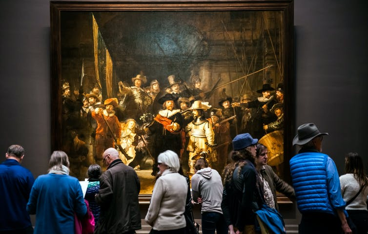 Amsterdam, Netherlands - April, 2017: Visitors watching 'The Night Watch,' Rembrandt's largest and most famous painting in Rijksmuseum's Gallery.