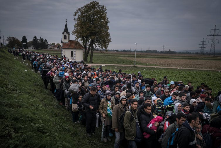 Sergey Ponomarev Migrants walk past the temple as they are escorted by Slovenian riot police to the registration camp outside Dobova Slovenia