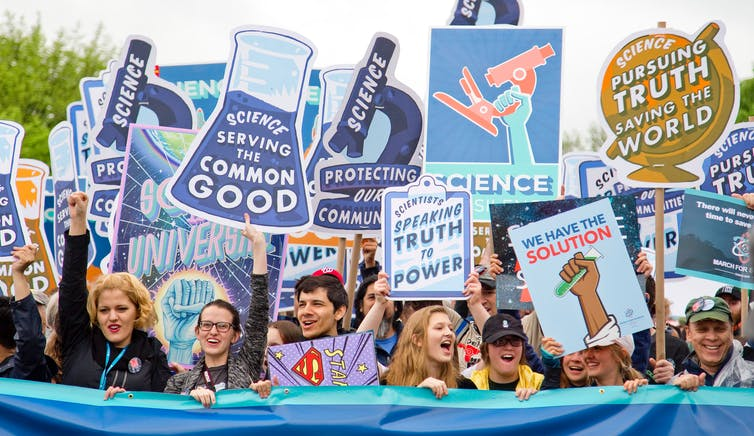 Adults holding up signs about the power of science behind a blue banner