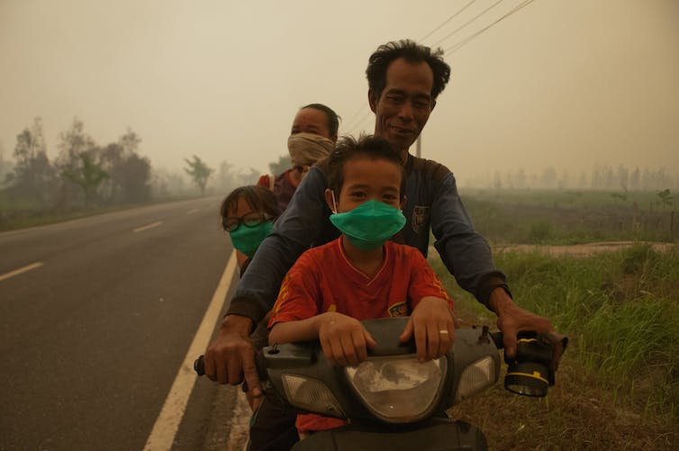A family rides through thick haze in Kalimantan, 2015. Aulia Erlangga/CIFOR, CC BY-NC-SA