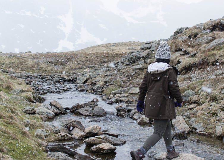 A person walking across a stream, with light snow falling.