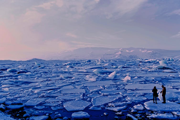Two people standing on a piece of ice, in front of a sea of broken ice sheets.
