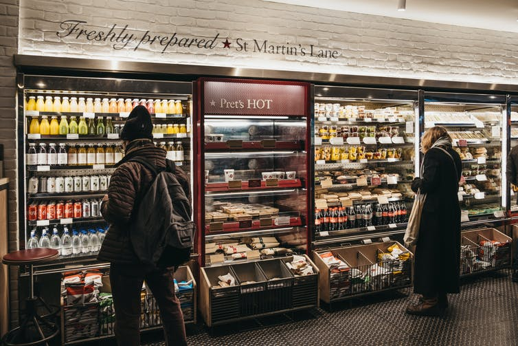 A wall of PRET with two customers looking at food and drink