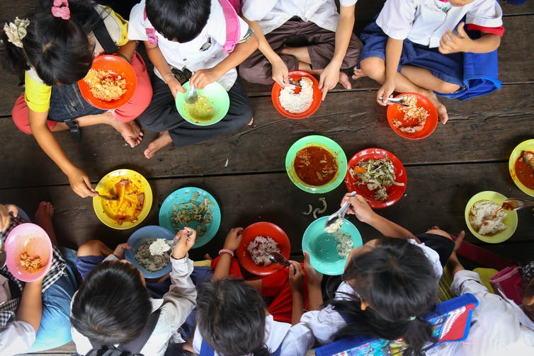 Children sat on floor eating food from coloured bowls
